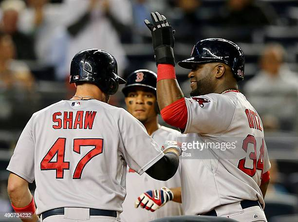 Travis Shaw of the Boston Red Sox is congratulated by teammates David Ortiz and Xander Bogaerts after Shaw drove them all in with a home run in the...