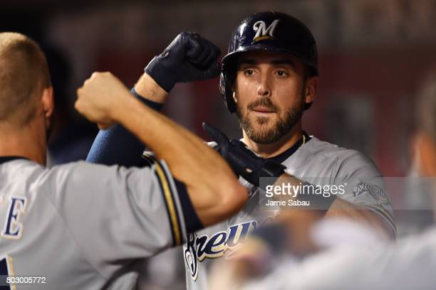 Travis Shaw of the Milwaukee Brewers celebrates in the dugout after his eighth inning home run against the Cincinnati Reds tied the game at Great...
