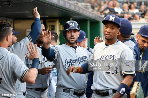 Travis Shaw of the Milwaukee Brewers celebrates with teammates in the dugout after coming around to score on an RBI single by Orlando Arcia in the...