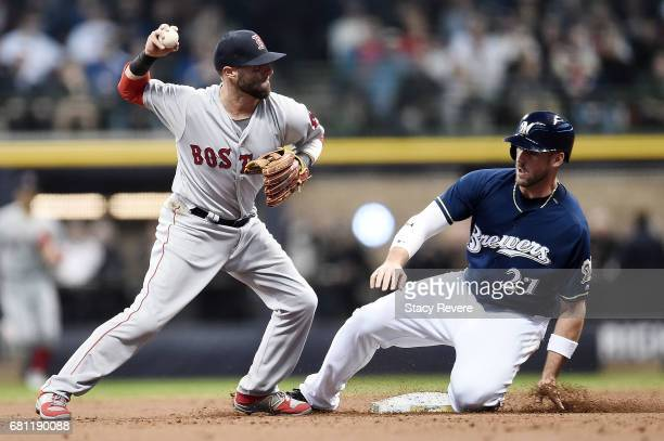 Travis Shaw of the Milwaukee Brewers is forced out at second base as Dustin Pedroia of the Boston Red Sox makes a throw to first base during the...