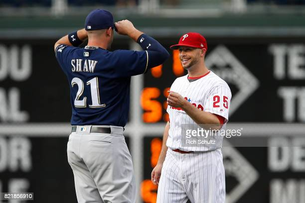 Travis Shaw of the Milwaukee Brewers talks with Daniel Nava of the Philadelphia Phillies before a game at Citizens Bank Park on July 21 2017 in...