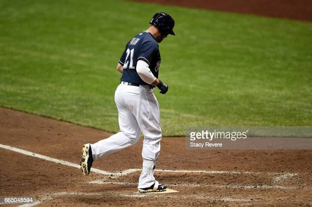 Travis Shaw of the Milwaukee Brewers touches home plate after a two run home run in the fourth inning of a game against the Colorado Rockies at...