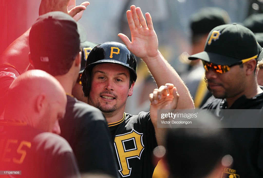 Travis Snider #23 of the Pittsburgh Pirates celebrates with teammates in the dugout after scoring on single to left by Russell Martin #55 (not in photo) during the MLB game against the Los Angeles Angels of Anaheim at Angel Stadium of Anaheim on June 23, 2013 in Anaheim, California. The Pirates defeated the Angels 10-9 in ten innings.