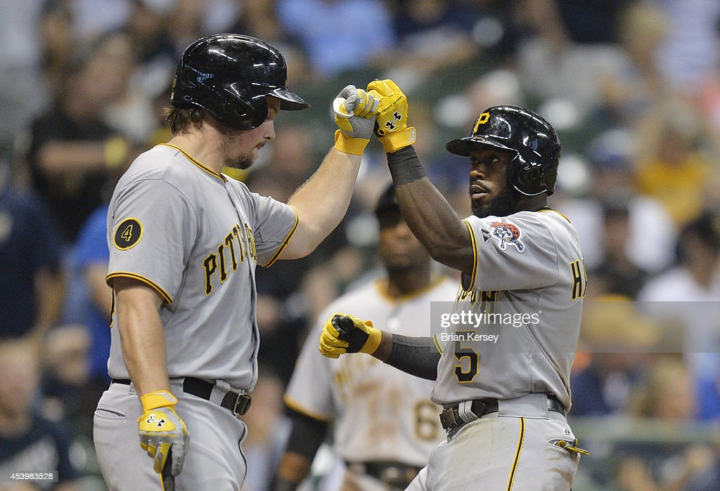 Travis Snider #23 of the Pittsburgh Pirates (L) fist bumps teammate Josh Harrison #5 after Harrison hit a two-run home run scoring Starling Marte during the eighth inning against the Milwaukee Brewers at Miller Park on August 22, 2014 in Milwaukee, Wisconsin.
