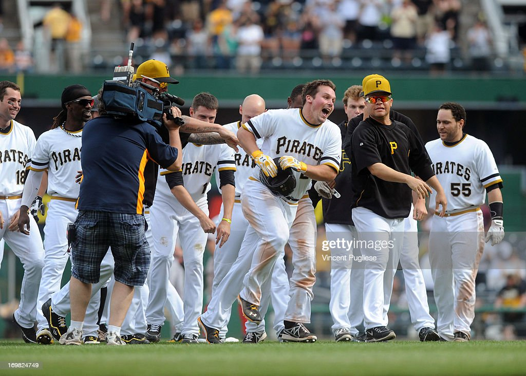 <a gi-track='captionPersonalityLinkClicked' href=/galleries/search?phrase=Travis+Snider&family=editorial&specificpeople=4959427 ng-click='$event.stopPropagation()'>Travis Snider</a> #23 of the Pittsburgh Pirates is mobbed by his teammates after driving in the winning run in the eleventh inning to defeat the the Cincinnati Reds 5-4 at PNC Park on June 2, 2013 in Pittsburgh, Pennsylvania.