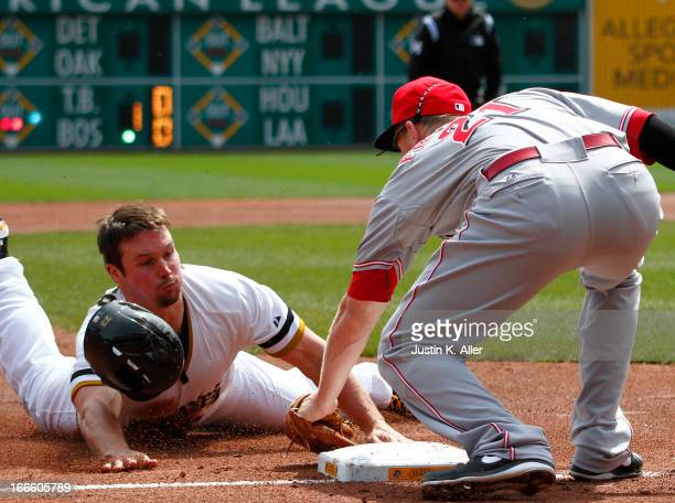 Travis Snider of the Pittsburgh Pirates is tagged out attempting to steal against Todd Frazier of the Cincinnati Reds in the first inning during the...
