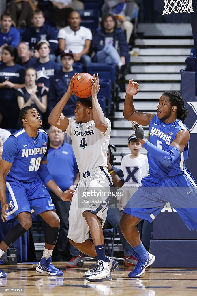 Travis Taylor #4 of the Xavier Musketeers looks to the basket against Shaq Goodwin #5 and D.J. Stephens #30 of the Memphis Tigers during the game at Cintas Center on February 26, 2013 in Cincinnati, Ohio. Xavier defeated Memphis 64-62.
