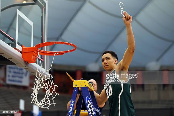 Travis Trice of the Michigan State Spartans celebrates by cutting down the net after defeating the Louisville Cardinals 76 to 70 in overtime of the...