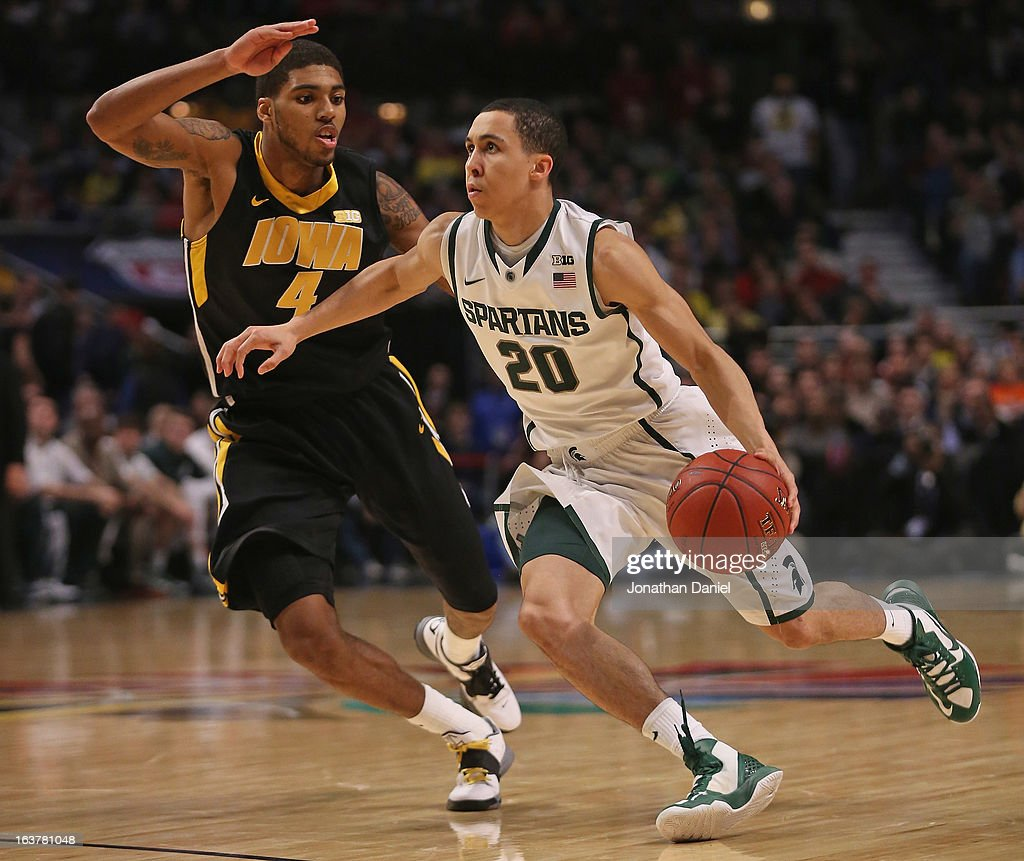 Travis Trice #20 of the Michigan State Spartans pushes the ball past Roy Devyn Marble #4 of the Iowa Hawkeyes during a quarterfinal game of the Big Ten Basketball Tournament at the United Center on March 15, 2013 in Chicago, Illinois.