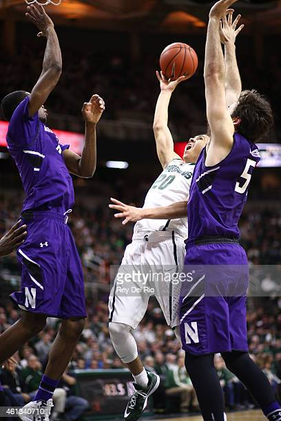 Travis Trice of the Michigan State Spartans shoots and draws a foul from Jeremiah Kreisberg of the Northwestern Wildcats at the Breslin Center on...