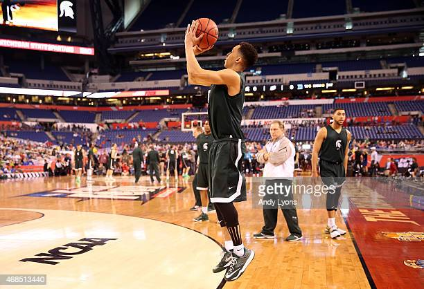 Travis Trice of the Michigan State Spartans shoots as head coach Tom Izzo looks on during practice for the NCAA Men's Final Four at Lucas Oil Stadium...
