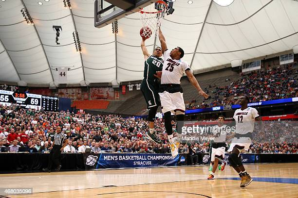 Travis Trice of the Michigan State Spartans shoots the ball against Wayne Blackshear of the Louisville Cardinals in the second half of the game...