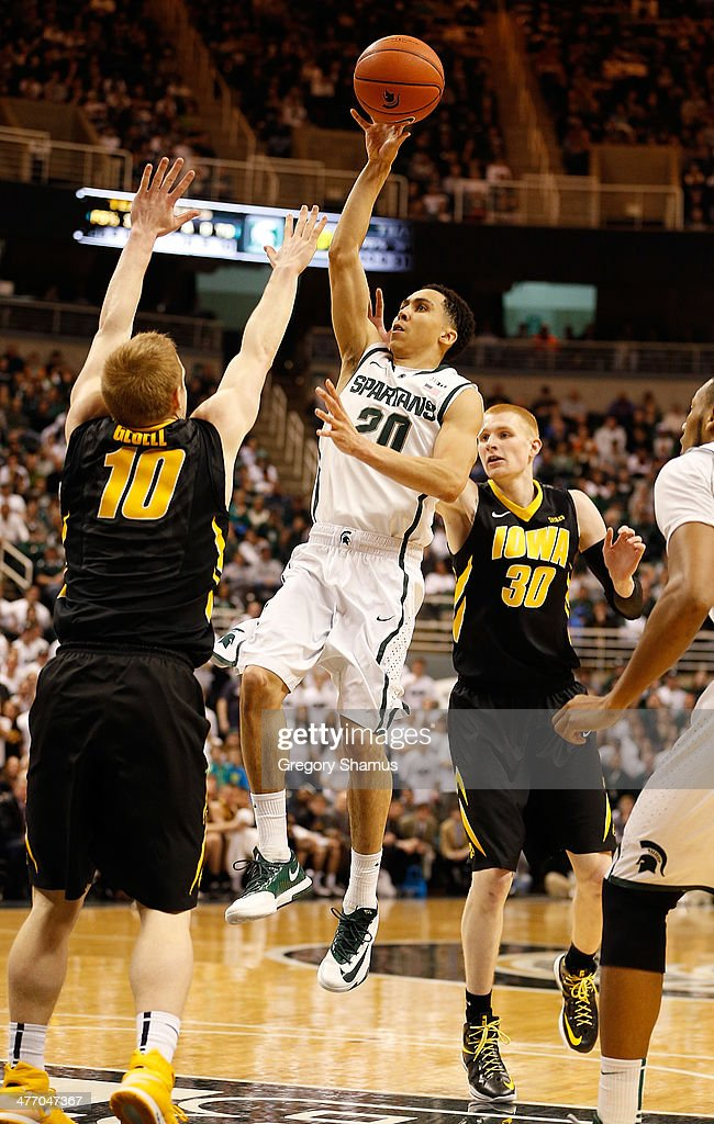 Travis Trice #20 of the Michigan State Spartans takes a second half shot between Mike Gesell #10 and Aaron White #30 of the Iowa Hawkeyes at the Jack T. Breslin Student Events Center on February 6, 2014 in East Lansing, Michigan. Michigan State won the game 86-76.