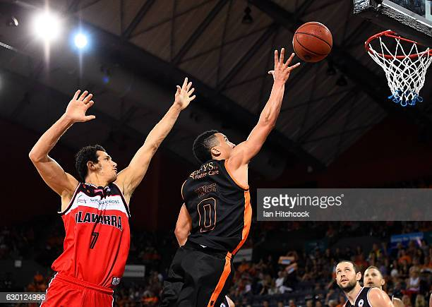 Travis Trice of the Taipans attempts a lay up past Oscar Forman of the Hawks during the round 11 NBL match between Cairns and Illawarra on December...
