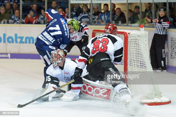 Travis Turnbull of Iserlohn Roosters and Justin Peters of Koeln Fredrik Eriksson of Koeln battle for the ball during the DEL match between Iserlohn...