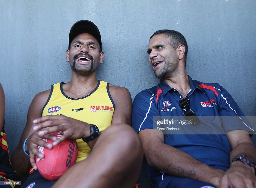 Travis Varcoe of the All Stars laughs with All Stars coach <a gi-track='captionPersonalityLinkClicked' href=/galleries/search?phrase=Michael+O%27Loughlin&family=editorial&specificpeople=215115 ng-click='$event.stopPropagation()'>Michael O'Loughlin</a> (R) during a press conference ahead of the AFL exhibition match between the Richmond Tigers and the Indigenous All Stars at Traeger Park on February 6, 2013 in Alice Springs, Australia.