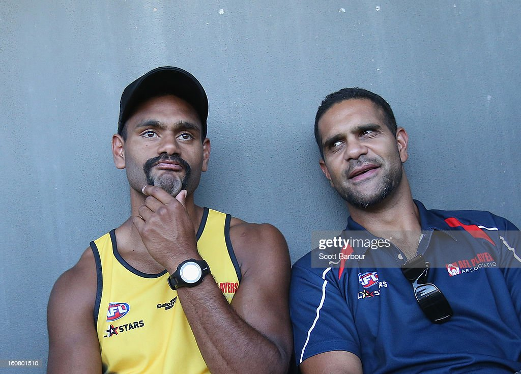 Travis Varcoe of the All Stars talks with All Stars coach <a gi-track='captionPersonalityLinkClicked' href=/galleries/search?phrase=Michael+O%27Loughlin&family=editorial&specificpeople=215115 ng-click='$event.stopPropagation()'>Michael O'Loughlin</a> (R) during a press conference ahead of the AFL exhibition match between the Richmond Tigers and the Indigenous All Stars at Traeger Park on February 6, 2013 in Alice Springs, Australia.