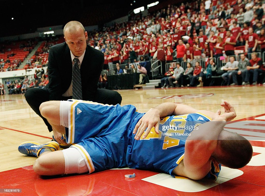 Travis Wear #24 of the UCLA Bruins is attended to after injuring his right ankle during the second half of the game against the Washington State Cougars at Beasley Coliseum on March 6, 2013 in Pullman, Washington.