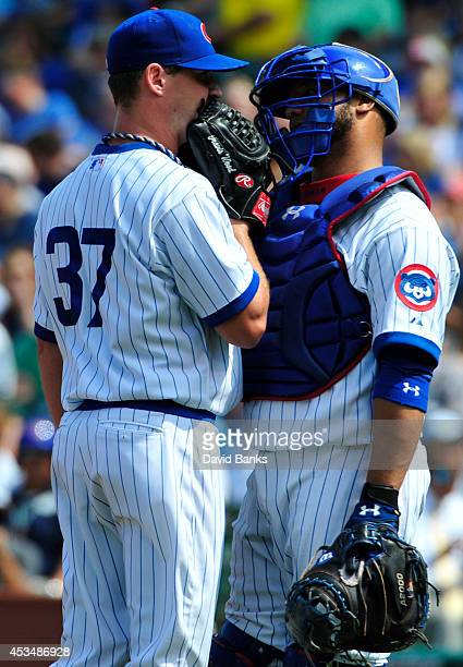 Travis Wood of the Chicago Cubs talks with Welington Castillo during the fifth inning of a game against the Tampa Bay Rays on August 10 2014 at...