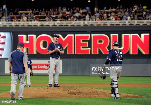 Travis Wood of the San Diego Padres reacts as manager Andy Green and catcher Austin Hedges head to the mound to relieve him from the game against the...