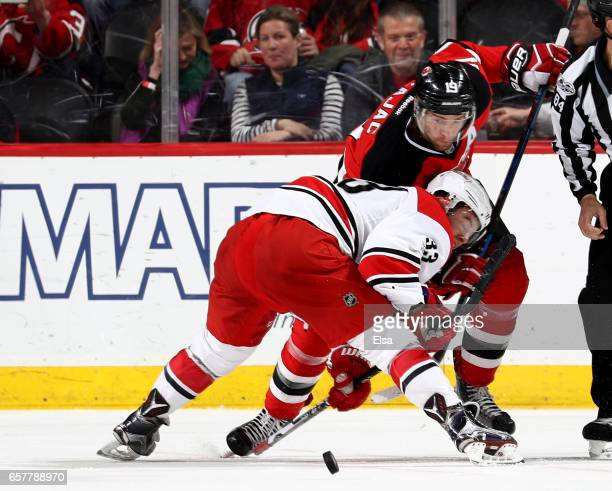 Travis Zajac of the New Jersey Devils and Derek Ryan of the Carolina Hurricanes fight for the puck in the second period on March 25 2017 at...