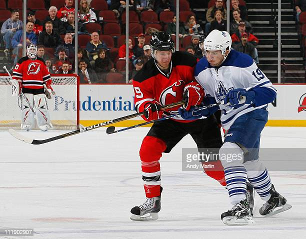 Travis Zajac of the New Jersey Devils and Joffrey Lupul of the Toronto Maple Leafs battle for position during the game at the Prudential Center on...