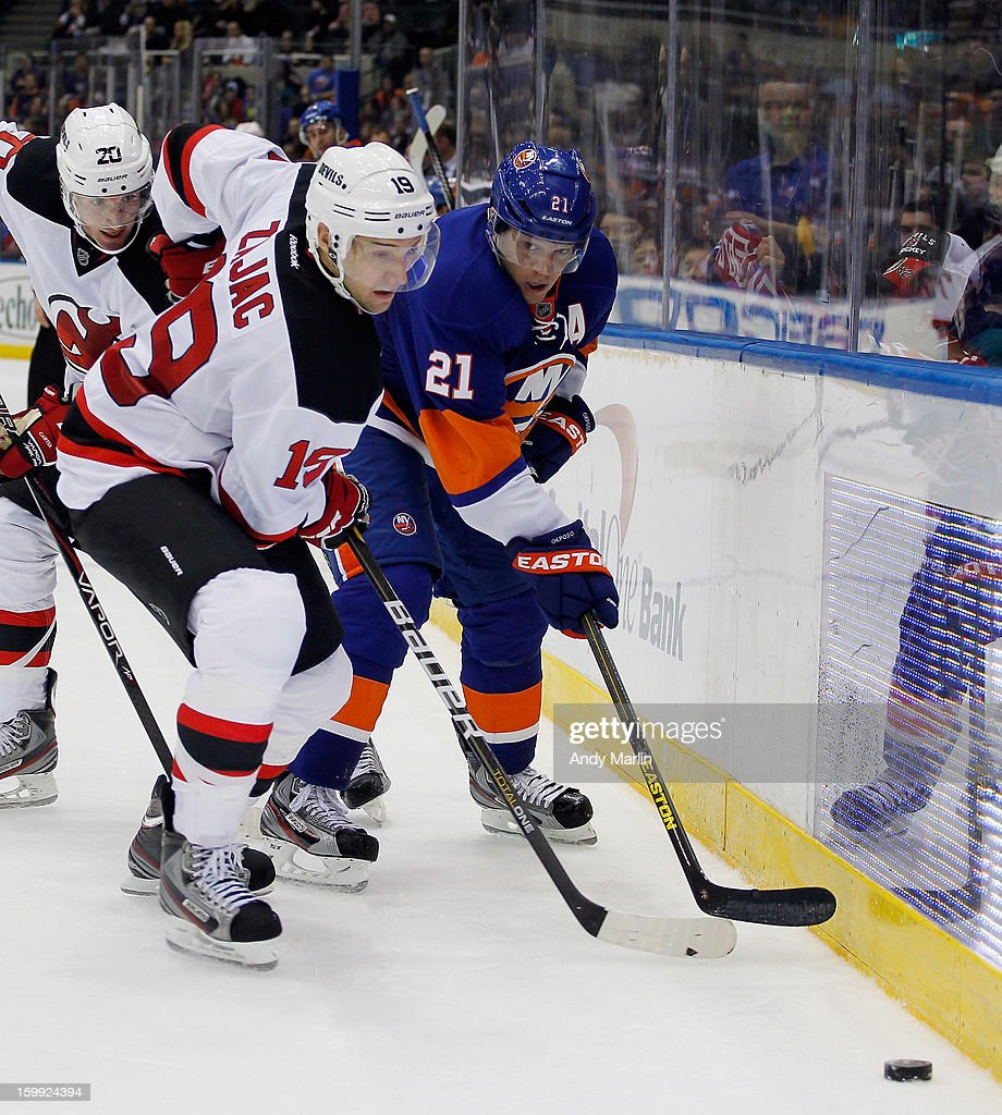 Travis Zajac #19 of the New Jersey Devils and Kyle Okposo #21 of the New York Islanders pursue a loose puck during the Islanders home opener at the Nassau Coliseum on January 19, 2013 in Uniondale, New York.