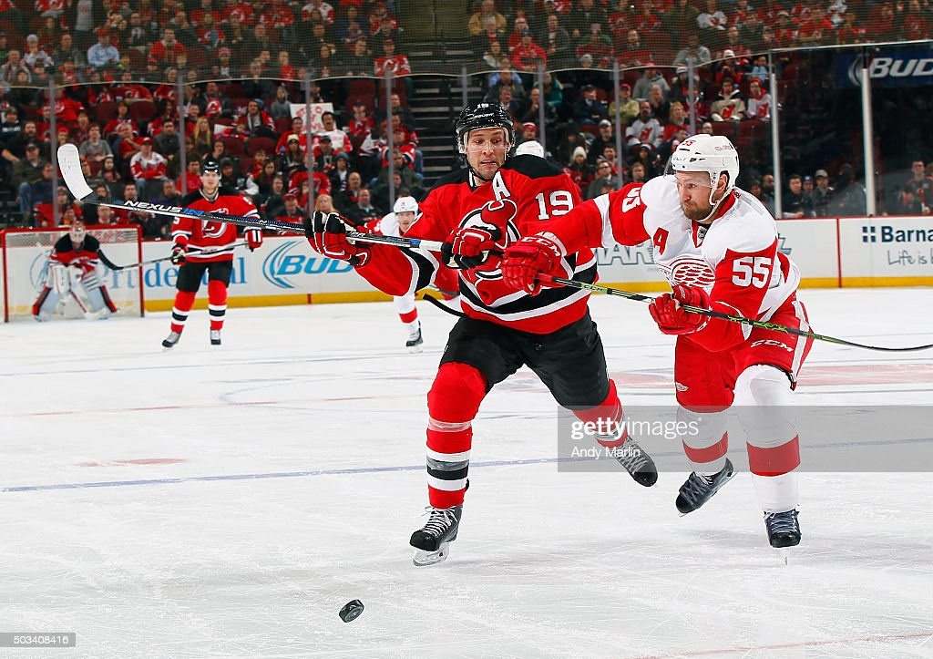 Travis Zajac #19 of the New Jersey Devils and Niklas Kronwall #55 of the Detroit Red Wings pursue a loose puck during the game at the Prudential Center on January 4, 2016 in Newark, New Jersey. The Red Wings defeated the Devils 1-0.