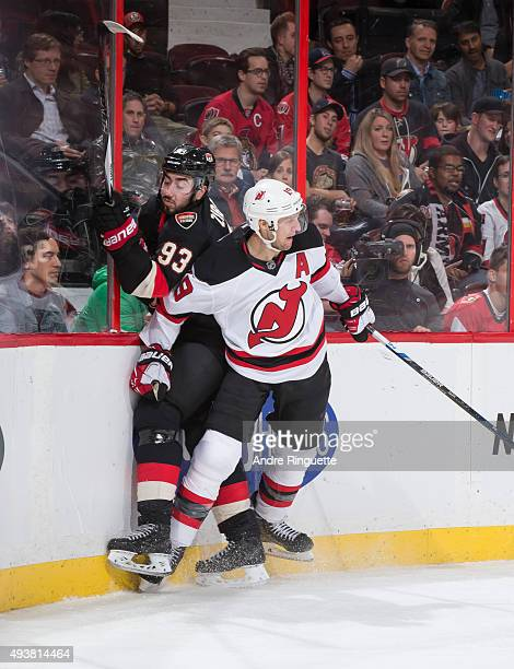 Travis Zajac of the New Jersey Devils bodychecks Mika Zibanejad of the Ottawa Senators into the end boards at Canadian Tire Centre on October 22 2015...