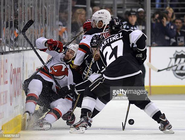 Travis Zajac of the New Jersey Devils is checked by Jeff Carter of the Los Angeles Kings in the first period alongside Alec Martinez of the Kings in...