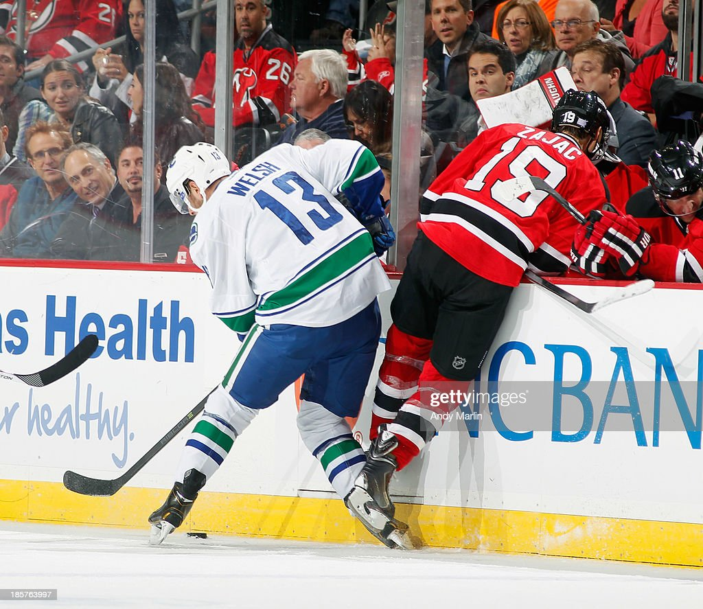 Travis Zajac #19 of the New Jersey Devils is checked off the puck near the Devils bench by Jeremy Welsh #13 of the Vancouver Canucks during the game at the Prudential Center on October 24, 2013 in Newark, New Jersey.