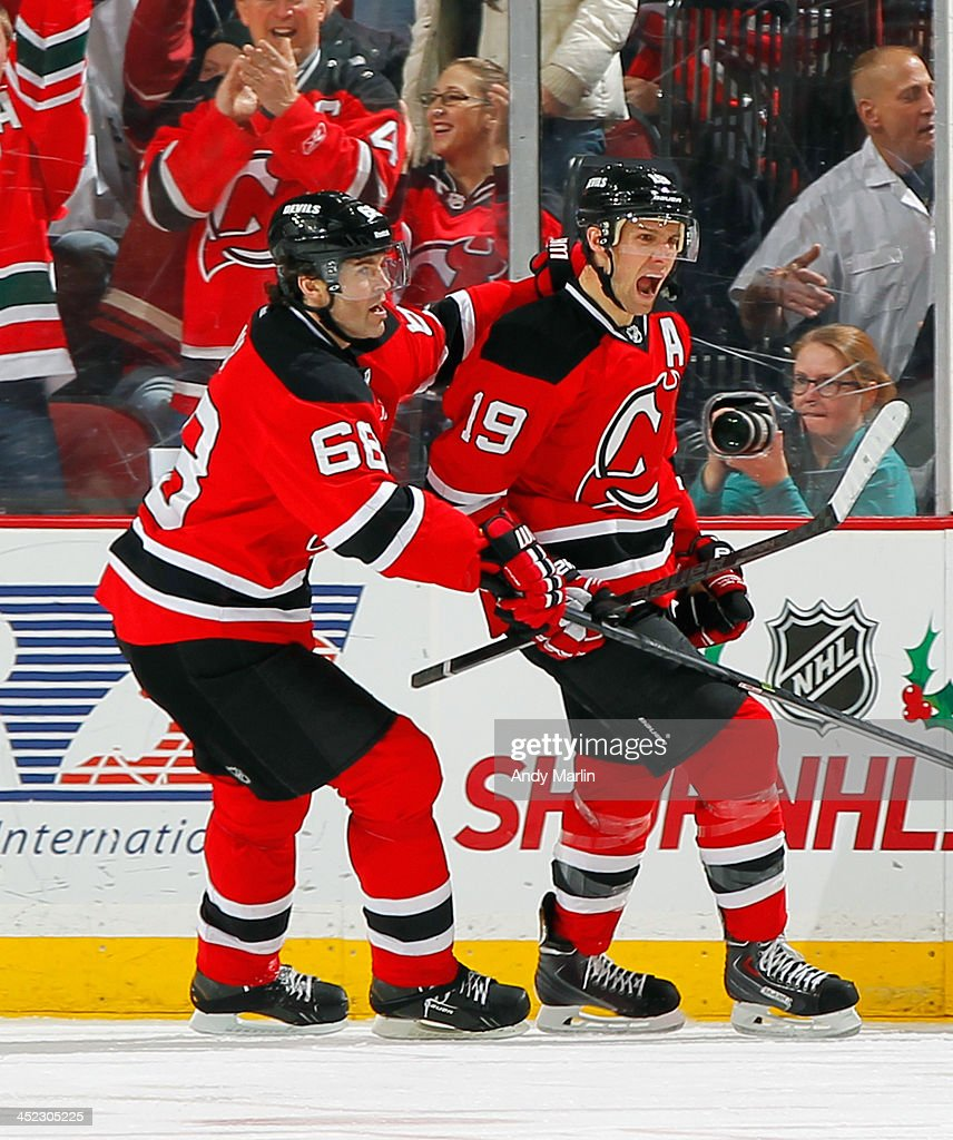 Travis Zajac #19 of the New Jersey Devils is congratulated by teammate Jaromir Jagr #68 after scoring a second-period goal against the Carolina Hurricanes during the game at the Prudential Center on November 27, 2013 in Newark, New Jersey.