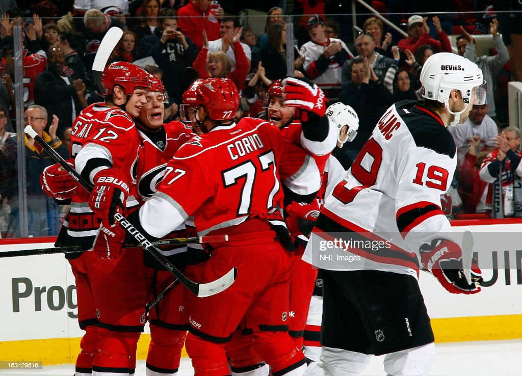 Travis Zajac #19 of the New Jersey Devils skates past the celebrating Carolina Hurricanes Eric Staal #12, Alexander Semin #28, Jiri Tlusty #19, Joe Corvo #77 and Tim Brent #37 following Semin's first-period goal during an NHL game on March 9, 2013 at PNC Arena in Raleigh, North Carolina.