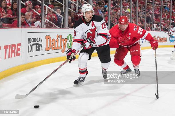 Travis Zajac of the New Jersey Devils skates with the puck in front of Mike Green of the Detroit Red Wings during an NHL game at Joe Louis Arena on...
