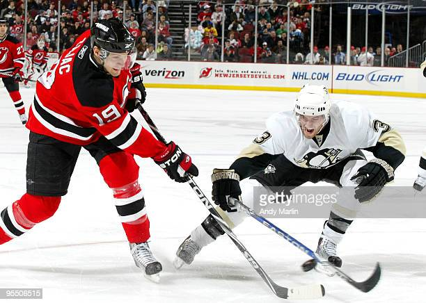 Travis Zajac of the New Jersey Devils takes a shot while being defended by Alex Goligoski of the Pittsburgh Penguins during their game at the...