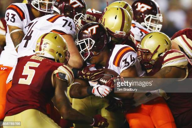 Travon McMillian of the Virginia Tech Hokies loses his helmet as he is tackled by the Boston College Eagles defense during the first half at Alumni...