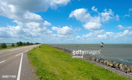 Trawler fishing on a lake along a dike : Stock Photo
