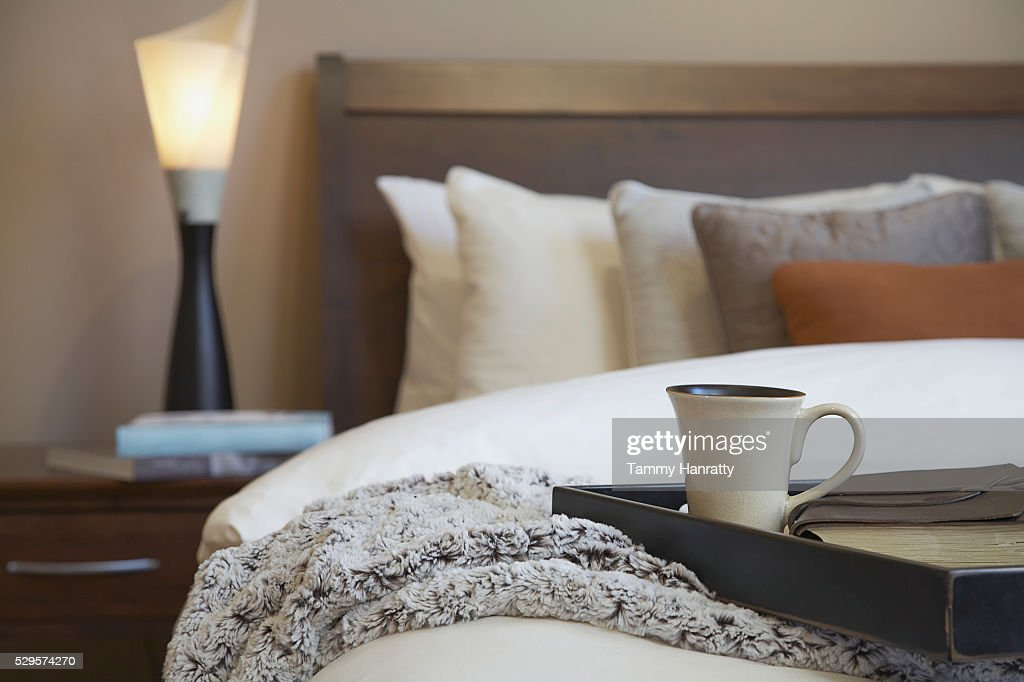 Tray and coffee cup on bed : Stock Photo