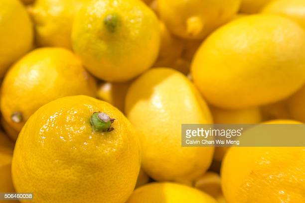 A tray full of fresh yellow lemons for sale in supermarket