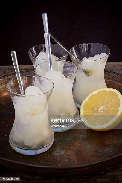 Tray of four glasses of lemon granita and lemon half