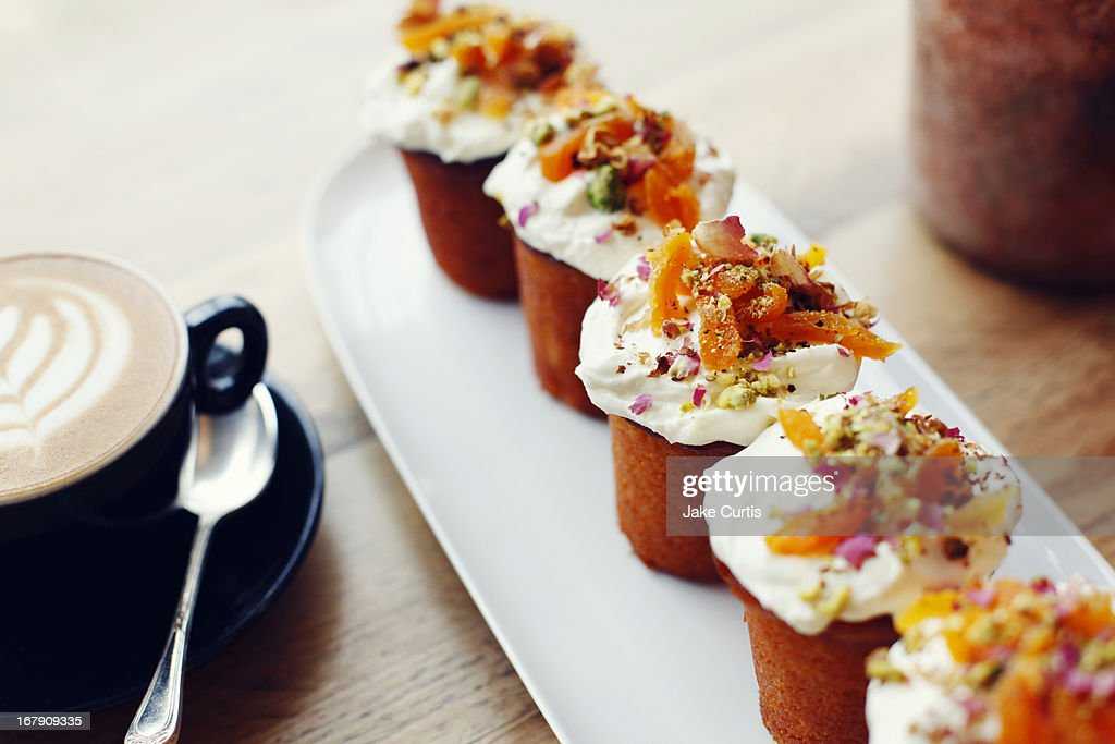 Tray of small cakes with colourful toppings : Stock Photo