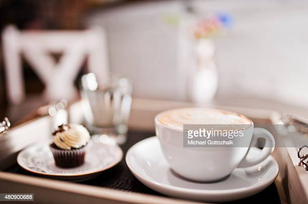 A tray with a cup of latte macchiato or coffee with milk or cappuccino next to a small cupcake and a glass of water on July 15 2015 in Berlin Germany