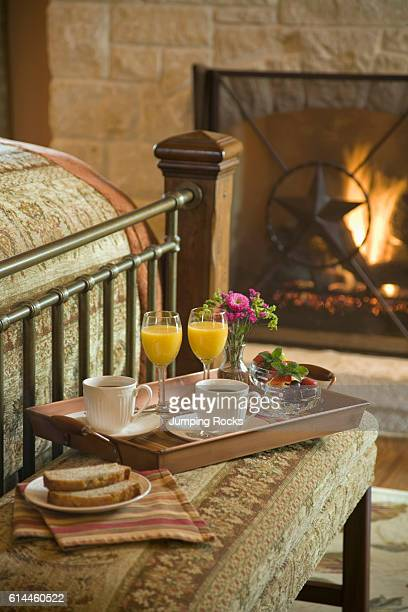 Tray with cups of coffee and orange juice on stool at foot of bed Texas