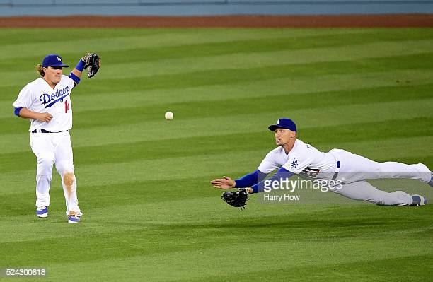 Trayce Thompson of the Los Angeles Dodgers dives to make an out of Adeiny Hechavarria of the Miami Marlins in front of Enrique Hernandez during the...