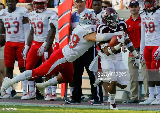 Trayveon Williams of the Texas AM Aggies is tackled by Evan Veron of the Nicholls State Colonels in the first quarter at Kyle Field on September 9...