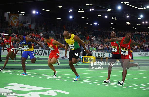 Trayvon Bromell of the United States crosses the line to win gold ahead of silver medallist Asafa Powell of Jamaica and bronze medallist Ramon...
