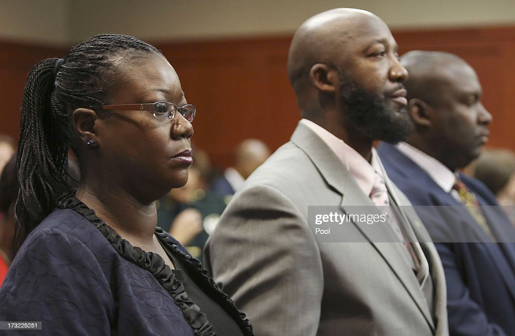 Trayvon Martin's parents, Sabrina Fulton (L) and Tracy Martin (C) stand during George Zimmerman's murder trial in Semimole circuit court July 10, 2013 in Sanford, Florida. Zimmerman has been charged with second-degree murder for the 2012 shooting death of Trayvon Martin.