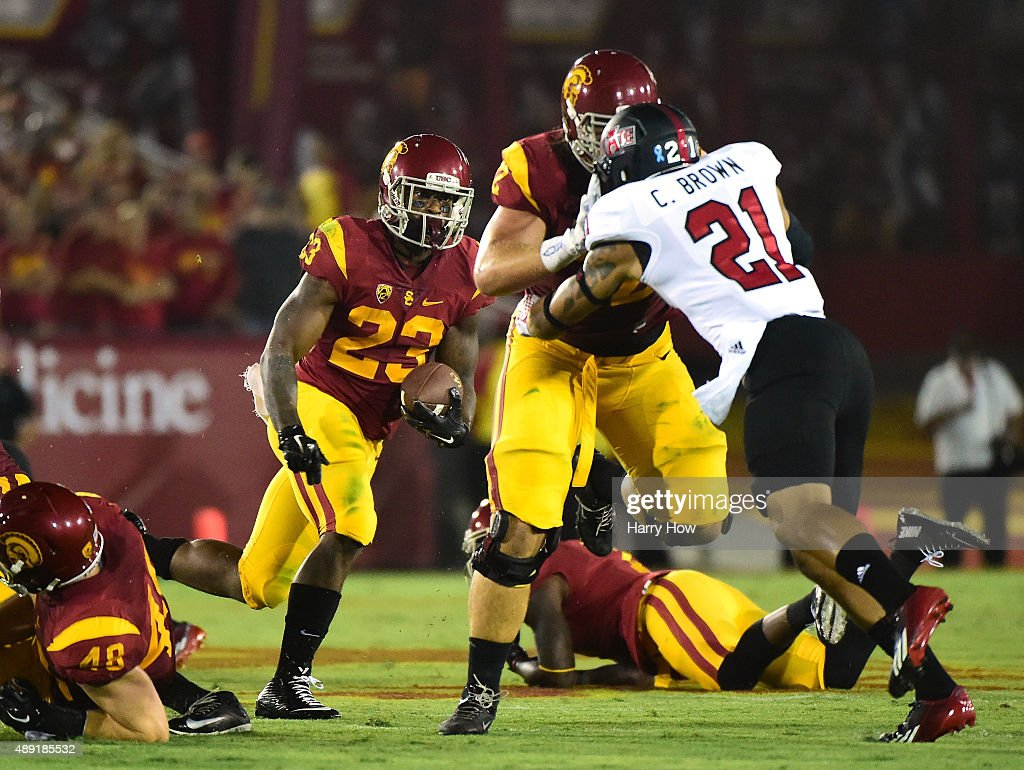 Tre Madden #23 of the USC Trojans follows the block of Khaliel Rodgers #62 on Cody Brown #21 of the Arkansas State Red Wolves at Los Angeles Coliseum on September 5, 2015 in Los Angeles, California.