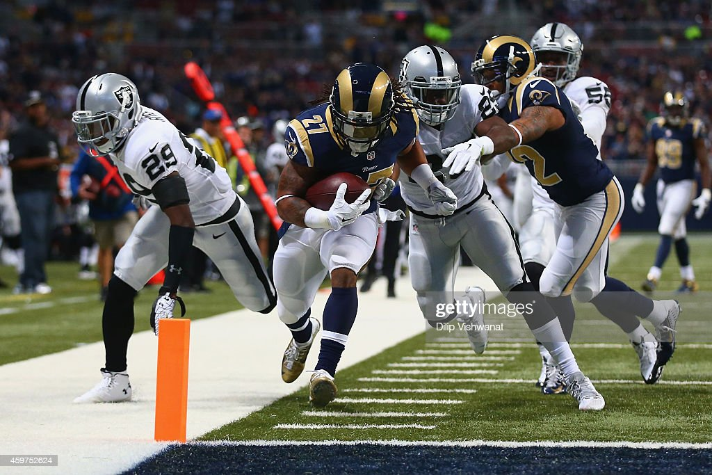 Tre Mason of the St Louis Rams scores a touchdown against Brandian Ross and DJ Hayden of the Oakland Raiders in the first quarter at the Edward Jones...
