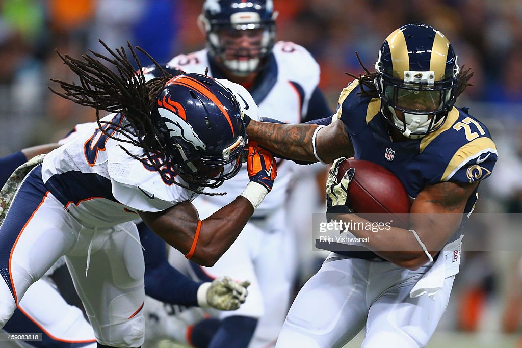 <a gi-track='captionPersonalityLinkClicked' href=/galleries/search?phrase=Tre+Mason&family=editorial&specificpeople=8222461 ng-click='$event.stopPropagation()'>Tre Mason</a> #27 of the St. Louis Rams slips a tackle attempt by <a gi-track='captionPersonalityLinkClicked' href=/galleries/search?phrase=Quinton+Carter&family=editorial&specificpeople=5631827 ng-click='$event.stopPropagation()'>Quinton Carter</a> #38 of the Denver Broncos in the first quarter at the Edward Jones Dome on November 16, 2014 in St. Louis, Missouri. The Rams beat the Broncos 22-7.